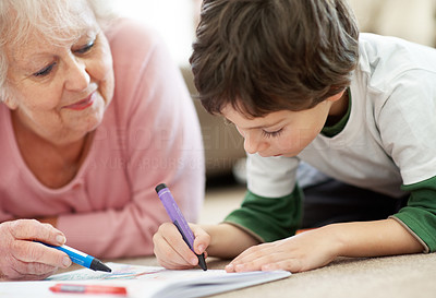 Sweet boy making drawing with his grandmother
