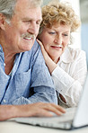 Retired senior couple surfing together on laptop