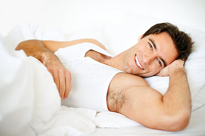 Handsome young guy waking up in morning on bed