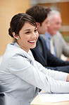 Smiling businesswoman in business meeting at office with colleagues in background