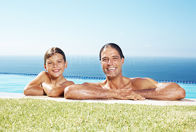 Happy father and son in water pool on a summer day