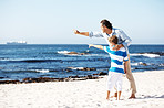Father and son both pointing at the sea - Copyspace