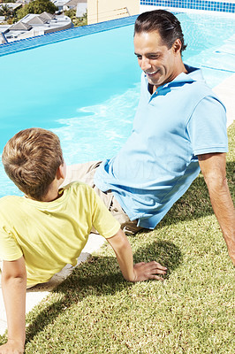 Happy man sitting along with his small son near water pool