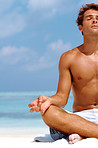 Cropped image of a young man meditating at the beach