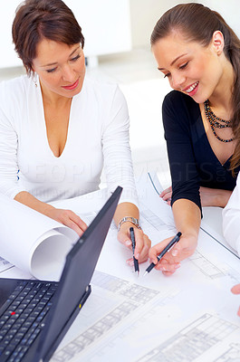 Buy stock photo Cropped shot of two coworkers discussing work while sitting at a desk