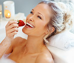 Happy young female eating a strawberry while in a bath tub
