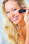 Closeup of a happy woman applying make up using a brush
