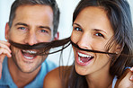 Playful couple teasing with fake mustache