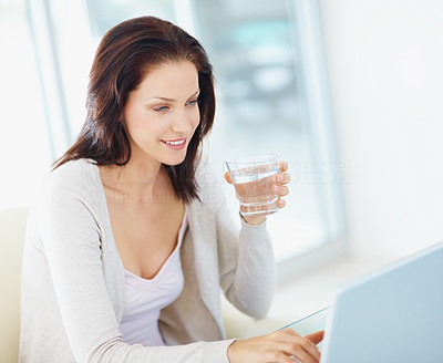 Young female holding a glass of water while using a laptop