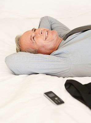 A happy mature man relaxing in bed with mobile phone