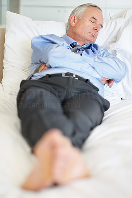 Tired matured business man lying in bed at hotel