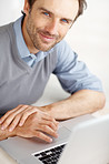 Smiling middle aged man looks at you while working on laptop