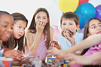 Little kids enjoying the birthday cake at a party