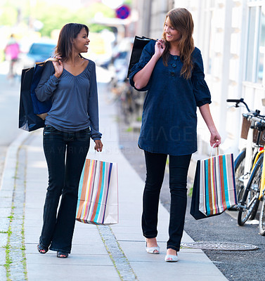 Happy young girls walking on street with shopping bags