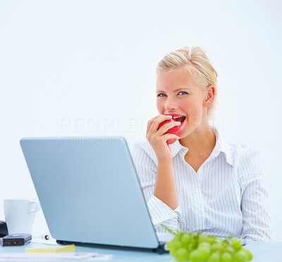 Beautiful business woman eating apple by laptop at desk