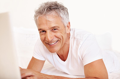 Happy mature man using laptop on bed