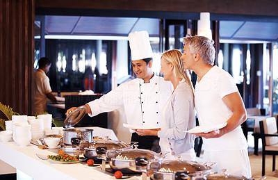Male chef serving food to happy mature couple