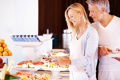 Handsome mature man and woman at hotel buffet