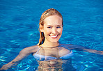Happy young female enjoying in the swimming pool