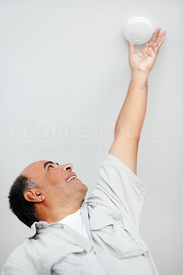Handy man reaching for an alarm to fix it