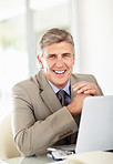 Relaxed mature business male with laptop smiling