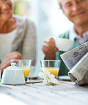 Old couple reading newspaper and having breakfast