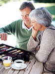 Old couple busy playing a game of backgammon