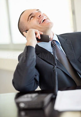 Cheerful middle aged business man over the telephone in office