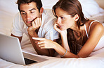 Young couple browsing the internet on a laptop in  bed