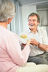 Happy retired man giving woman a present on birthday