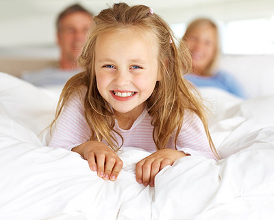 Happy little girl lying on bed with her parents in background