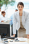 Confident business woman at desk with colleagues at the back