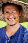 Closeup portrait of a Thai rice paddy worker wearing a traditional hat