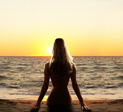 Buy stock photo Portrait of a beautiful woman sitting by the ocean enjoying the golden yellow sunset.  Attention buyer: This is really plastic fantastic photoshopping. This picture should only be used on webpages and it is not intended for print.