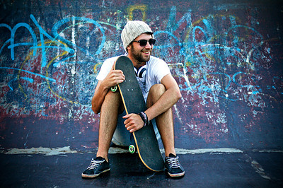 Buy stock photo Skateborder sitting in front of a graffitied wall holding his skateboard