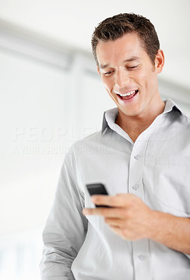 Cheerful middle aged man reading a text message on cellphone