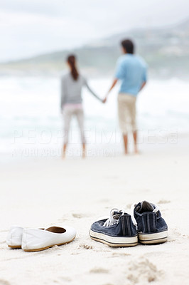 Couple relaxing on beach - Focus on the shoes in the foreground