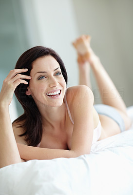 Happy young female lying in bed thinks about something