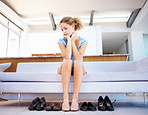 Portrait of a cute young girl sitting on couch and looking at sandals