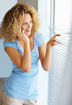 Young beautiful woman looking through window while speaking