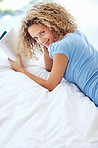 Portrait of attractive cute girl lying on bed with a book
