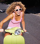 Closeup portrait of a happy young girl riding a scooter on road