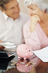 Unhappy couple with piggybank in front of them