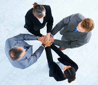 Buy stock photo Handshake and teamwork. Four business people making a pile of hands in a light and modern office.