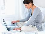 Pretty female sitting in bed using a laptop