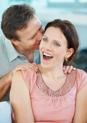 Mature man whispering a surprise into woman\'s ears