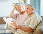 Elderly man with his wife going through documents on couch