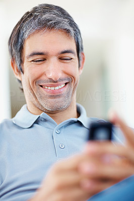 Happy man reading funny text message on mobile phone