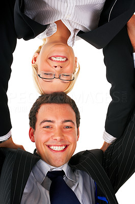 Buy stock photo Portrait of two business partners holding there heads together. Taken from below. Picture concept is united, strength, partnership.