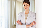 Confident young business woman leaning against a wall